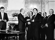 After their win in the recent general election, the new Fianna Fáil government, under the leadership of Charles Haughey, is sworn in and given their seals of office at a ceremony in Áras an Uachtaráin. President Hillery presents the seal of office to Bertie Ahern at the ceremony in the Arás.<br /> 10 March 1987