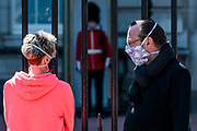 Tourists in masks at Buckingham Palace - People are out exercising on bikes and on foot, some in masks and some not. Central London is pretty crowded as the sun comes out again. The 'lockdown' continues for the Coronavirus (Covid 19) outbreak in London.