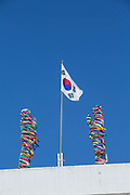 The South Korean flag at the Goseong Unification Observatory on 06th February 2016 in South Korea. Open specially for the 2018 Winter Olympic and Paralympics, the site is also known as the Geumgangsan Observatory, and is a military area normally restricted to the public. Views stretch into North Korea overlooking the Geumgangsan Mountains and the Korean Demilitarised Zone, a strip of land running across the Korean Peninsula deciding the two nations. The Path to Peace tour was organised by PyeongChang and The Ministry of Culture, Sports and Tourism.
