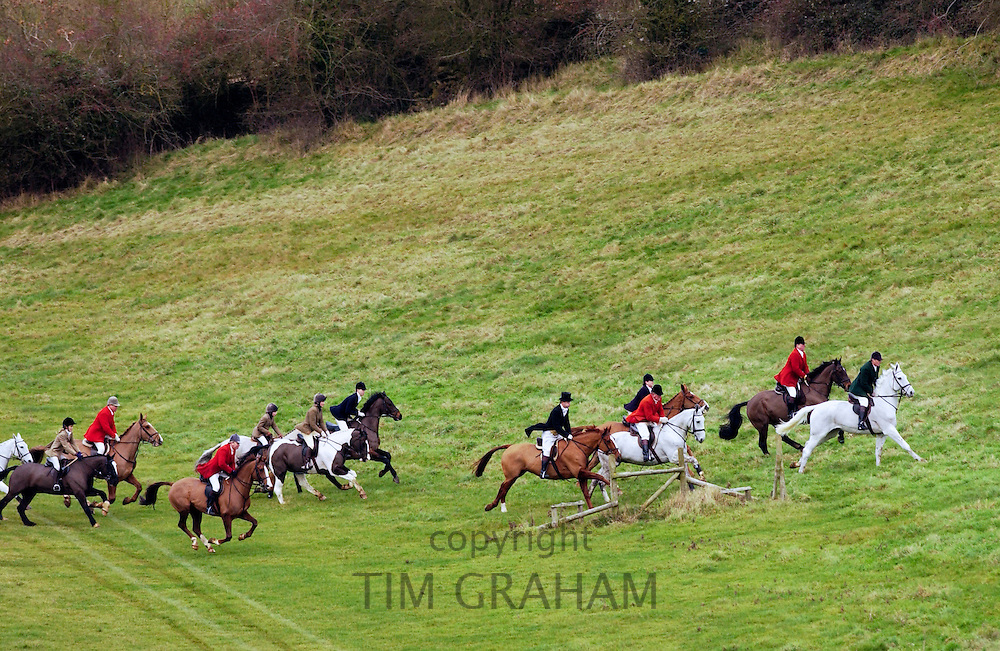 Huntsmen riding across fields during the Heythrop New Year's Day Hunt, Oxfordshire