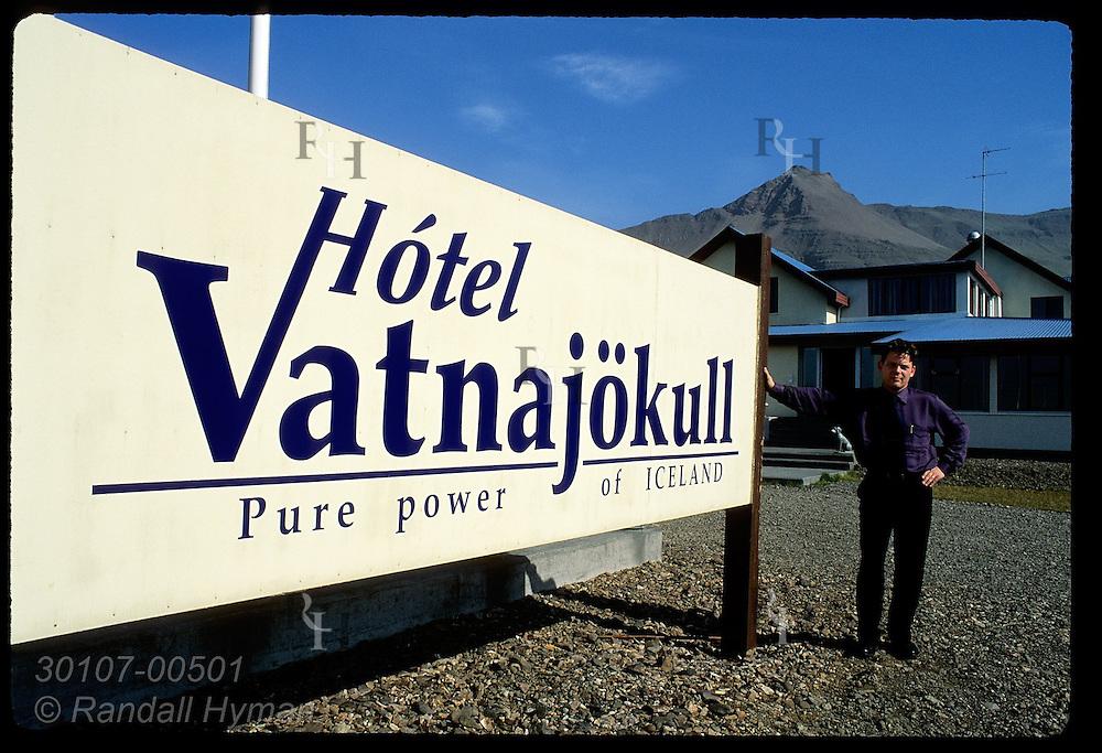 Manager Gudmundur Johansson poses beside Hotel Vatnajokull sign in front of the hotel; Hofn, southeast Iceland.