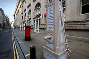 City of London England UK March 2021<br />The site of a WELL originating from 1282.<br />By the roadside, on the pavement directly outside the south-east corner of the Royal Exchange, you will find the Cornhill Pump, a true remint from days long gone.<br /> <br /> The pump is from 1799 and was fpaid for by several City of London institutions. The Bank of England and the East India Company being the main contributors. The inscription says: 'On This Spot A Well Was First Made And A House Of Correction Built Thereon. By Henry Wallis Mayor Of London In The Year 1282.'