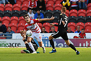 Doncaster Rovers forward John Marquis (9) gets away from Portsmouth FC defender Matthew Clarke (5) and Portsmouth FC midfielder Tom Naylor (7) during the EFL Sky Bet League 1 match between Doncaster Rovers and Portsmouth at the Keepmoat Stadium, Doncaster, England on 25 August 2018.Photo by Ian Lyall.