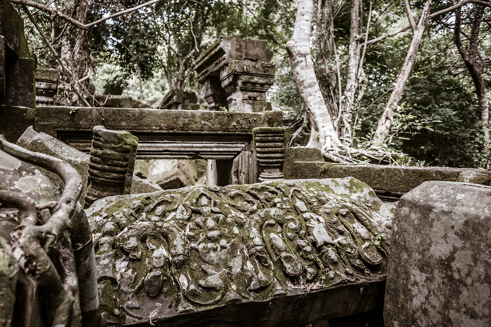 """Prasat Beng Mealea (Khmer: ប្រាសាទបឹងមាលា), meaning """"lotus pond"""", is a Hindu temple built of sandstone to worship Vishnu during the Angkor Wat period (early 12th century). It is located 40km east of the main group of temples at Angkor, Cambodia, on the ancient royal highway to Preah Khan Kompong Svay. The temple complex lies in ruins and overgrown by trees."""