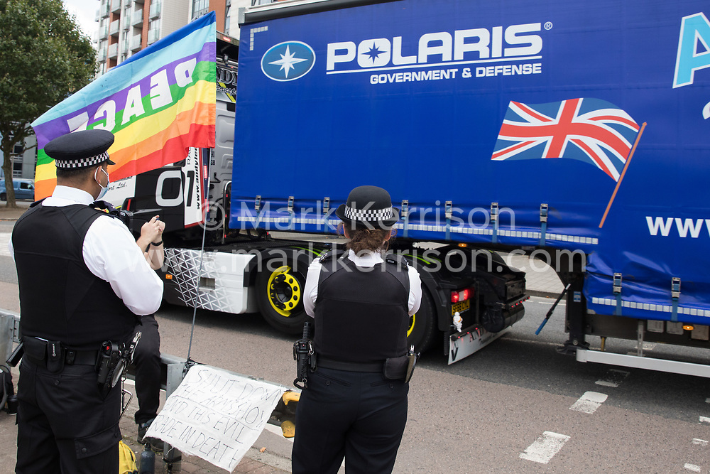 London, UK. 6th September, 2021. Metropolitan Police officers observe a heavy goods vehicle approaching ExCeL London as preparations take place for the DSEI 2021 arms fair. The first day of week-long Stop The Arms Fair protests outside the venue for one of the world's largest arms fairs was hosted by activists calling for a ban on UK arms exports to Israel.