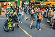 Authorities remain vigilant with Police and Paramedics highly visible - The market reopening is signified by the ringing of the bell and is attended by Mayor Sadiq Khan. Tourists and locals soon flood back to bring the area back to life. London 14 Jun 2017