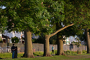 Beneath tall ash trees, a  romantic couple walk behind a runner - both park users in Ruskin Park in the borough of Lambeth, on 7th June 2021, in south London, England.