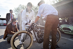 **CAPTION CORRECTION. Picture originally sent with wrong date. Picture was taken TODAY 11/09/2015** © licensed to London News Pictures. 11/09/2015<br /> Goodwood Revival Weekend, Goodwood, West Sussex. UK.<br /> The Goodwood Revival is the world's largest historic motor racing event. Competitors and enthusiasts dress in period fashions recreating the glorious days of the race circuit.<br /> Pictured mechanics prepare a vintage Peugot motorbike.<br /> <br /> Photo credit : Ian Whittaker/LNP