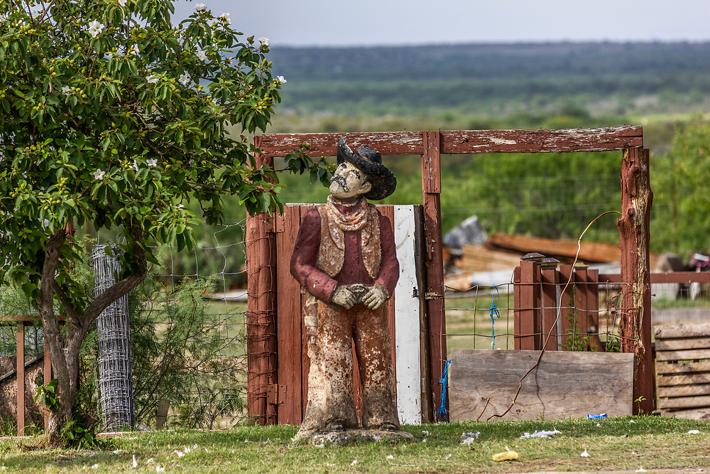 Giant stone cowboy stands by the roadside, Rural landscape, Zapata County, Texas, USA