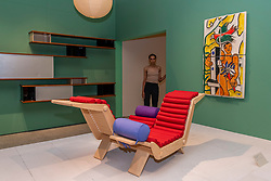 """© Licensed to London News Pictures. 17/06/2021. LONDON, UK. A model poses next to """"Double Chaise Longue"""", 1952. Preview of """"Charlotte Perriand: The Modern Life"""" exhibition at the Design Museum in Kensington. Charlotte Perriand's (1903-1999) pioneering furniture designs shaped the 20th century and helped define the modern interior.  The exhibition marks the 25th anniversary of her first exhibition at the Design Museum in 1996 and runs 19 June to 5 September 2021.  Photo credit: Stephen Chung/LNP"""