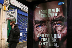 © Licensed to London News Pictures. 01/02/2021. London, UK. A woman wearing a protective face covering walks past the government's 'Look him in the eyes - And tell him the risk isn't real.' awareness publicity campaign poster in north London.  Covid-19 infection rates are continuing to drop across London. According to a Government scientific adviser, the UK could be easing out of restrictions in March and back to almost normal by summer if vaccines are 70 to 80 per cent effective at blocking transmission. Photo credit: Dinendra Haria/LNP