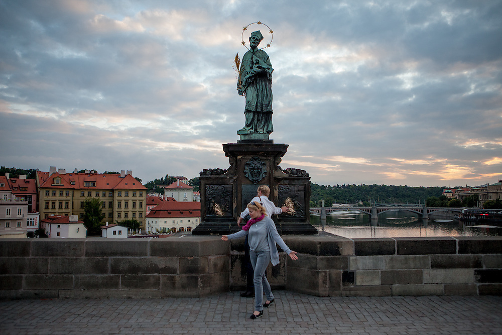 Early morning visitors at Charles Bridge at the St. John of Nepomuk Statue. Touching the statue is a Prague ritual. It is supposed to bring good luck and to ensure that you return to Prague soon.