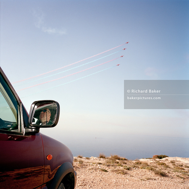 Ground commentator pilot of the Red Arrows, Britain's RAF aerobatic team watches training flight from air conditioned car.