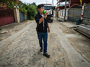14 JULY 2015 - THAILAND:  A water department worker uses a bullhorn to alert people to free water deliveries from the Thai army in Pathum Thani province near Bangkok. The drought that has crippled agriculture in central Thailand is now impacting residential areas near Bangkok. The Thai government is reporting that more than 250,000 homes in the provinces surrounding Bangkok have had their domestic water cut because the canals that supply water to local treatment plants were too low to feed the plants. Local government agencies and the Thai army are trucking water to impacted communities and homes. Roads in the area have started collapsing because of subsidence caused by the retreating waters. Central Thailand is contending with drought. By one estimate, about 80 percent of Thailand's agricultural land is in drought like conditions and farmers have been told to stop planting new acreage of rice, the area's principal cash crop.      PHOTO BY JACK KURTZ