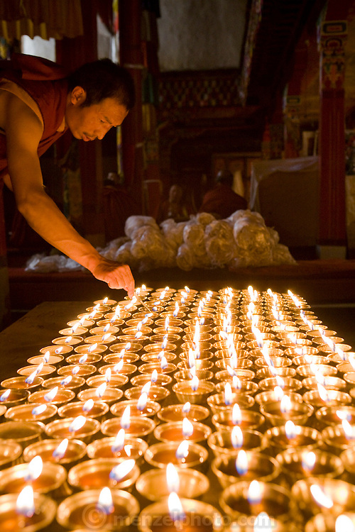 A monk lights candles as he prepares for prayer at a Buddhist monastery in the Tibetan Plateau.