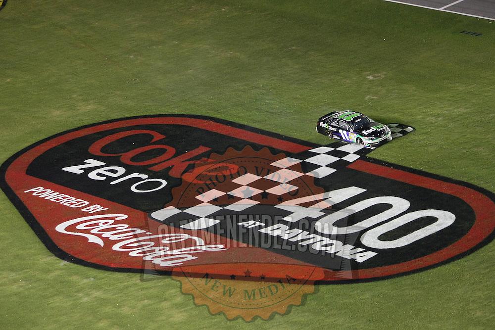 NASCAR Sprint Cup driver Denny Hamlin (11) spins through the infield during the NASCAR Coke Zero 400 Sprint series auto race at the Daytona International Speedway on Saturday, July 6, 2013 in Daytona Beach, Florida.  (AP Photo/Alex Menendez)