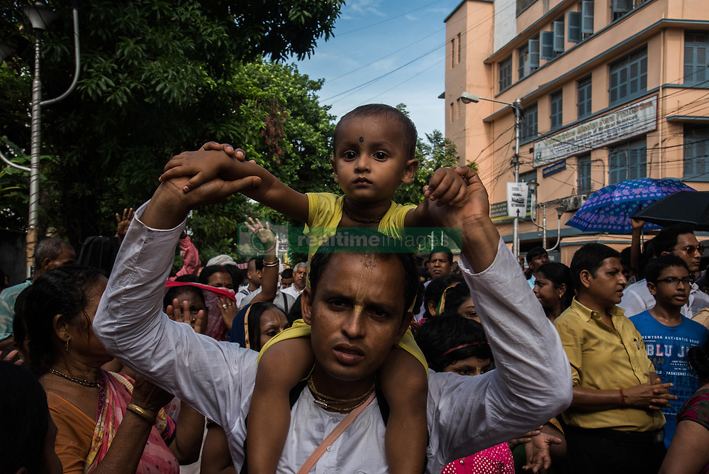 June 26, 2017 - Kolkata, West Bengal, India - A devotee is walking in the procession with his daughter on his shoulders as she is too small to walk herself in the procession during rath yatra in Kolkata, India on 25.6.2017. Rath Yatra or the cart festival is more than 5000 years old festival which is mainly celebrated in Puri, Orissa with great zeal. This eminent festival marks the return of Lord Krishna to Vrindavan with his elder brother balabhadra and sister Subhadra. The rath yatra is a journey in a chariot accompanied by the public and it is usually celebrated in the month of June or July. Rath yatra is also celebrated in different parts of West Bengal under the supervision of the Iscon temple. (Credit Image: © Sushavan Nandy/NurPhoto via ZUMA Press)