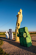"In the Car Art Reserve at Carhenge, Jim Reinders arranged the ""Ford Seasons"" artwork using four Fords as inspired by Vivaldi's Four Seasons. Carhenge replicates England's Stonehenge using vintage American automobiles, near Alliance, Nebraska, in the High Plains region, USA. After studying Stonehenge in England, years later, Jim Reinders recreated the physical size and placement of Stonehenge's standing stones in summer 1987, helped by 35 family members. Reinders said, ""It took a lot of blood, sweat, and beers."" Carhenge was built as a memorial to Reinders' father. 39 automobiles were arranged in the same proportions as Stonehenge with the circle measuring a slightly smaller 96 feet (29m) in diameter. Some autos are held upright in pits five feet deep, trunk end down, while other cars are placed to form the arches and welded in place. All are covered with gray spray paint. The heel stone is a 1962 Cadillac. Reinders donated Carhenge to the Friends of Carhenge, who gifted it to the Citizens of Alliance in 2013."