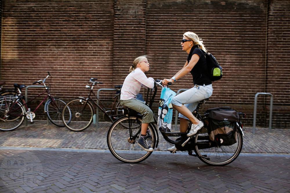 Een meisje zit achterstevoren op een bagagerek voorop de fiets bij een vrouw