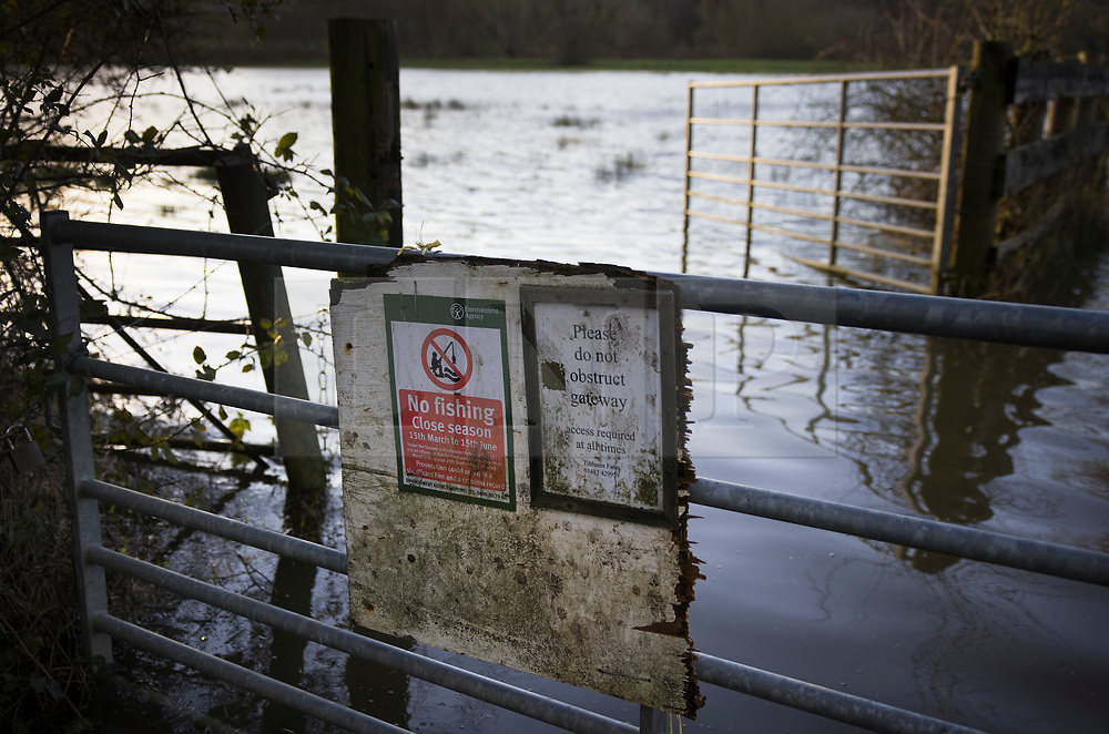 © Licensed to London News Pictures. 21/01/2021. Peasmarsh, UK. A no fishing sign adorns a gate as floodwater from the River Wey spills out over fields in Peasmarsh in Surrey after days of rain from Storm Christoph. Photo credit: Peter Macdiarmid/LNP