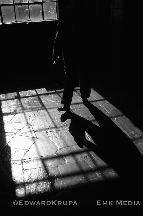 Silhouette and shadow of a man carrying a breifcase.