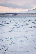 Cracking ice at Isfjord Radio, and old radio telecommunications building, now accomodation for tourists in Spitsbergen. Spitsbergen is the largest island of the arctic archipelago Svalbard, of NorwaySpitsbergen is the largest island of the arctic archipelago Svalbard, of Norway