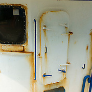 The rusty door to a wheelhouse on a fishing boat in Gloucester Massachusetts harbor