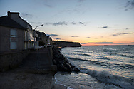 The sun sets over the Atlantic Ocean in Arromanches, Normandy, France. In the days after D-Day the Allies built a large artificial port here called Mulberry Harbour, the remains of which are still visible, including three segments on the right side of this picture.