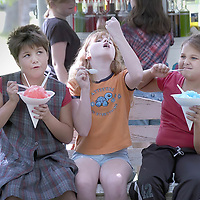 Brianna Sims, 8, Kaliegh Peloquin, 10, and Mariah Sims, 10, make faces while eating extra large snow cones at the Genevieve Miller Hitchcock Public Library Festival in the Park at the Gordon and Ursula Latimer Park on Berry, 05/22/04. (Photo by Kim Christensen)