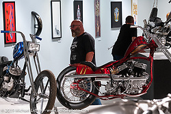 """Canadian Scotty Busch checking out art on the walls with Josh Sheehan's Buzzards Luck Frisco-style chopper in the foreground. Built with a customized 1936 VL Frame and a 1947n 45"""" Flathead bottom and 1953 K Model top end. On view in the What's the Skinny Exhibition (2019 iteration of the Motorcycles as Art annual series) at the Sturgis Buffalo Chip during the Sturgis Black Hills Motorcycle Rally. SD, USA. Thursday, August 8, 2019. Photography ©2019 Michael Lichter."""
