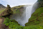 "The Skogarfoss waterfall roars over the cliffs at Skogar with the ""Horn"" rock formation looking on"