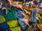 30 JUNE 2016 - BANGKOK, THAILAND: A porter tears down a customer's flower stall in the Pak Khlong Talat sidewalk market. Sidewalk vendors around Pak Khlong Talat, Bangkok's famous flower market, face eviction if they reopen on July 1. As a part of the military government sponsored initiative to clean up Bangkok, city officials have been trying to shut down the sidewalk vendors around the flower market. The vendors were supposed to be gone by the end of March, but city officials relented at the last minute with a compromise allowing vendors to stay until June 30. When vendors dismantled their booths after business on June 30, they weren't sure if they will be allowed to reopen July 1. Some vendors have moved to new locations approved by the government but many have not because they can't afford the higher rents in the new locations.     PHOTO BY JACK KURTZ