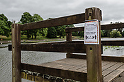 MERTHYR TYDFIL, Wales - 04 JUNE 2020 - Cyfarthfa Park lake with a sign explaining to social distance and keep 2 meters apart.