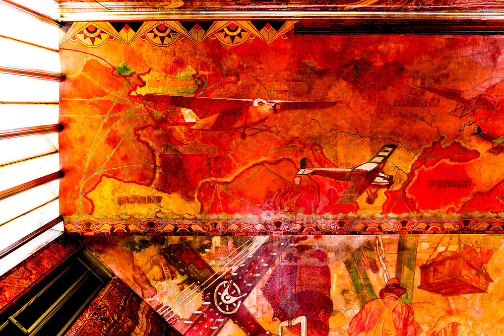 """This section of the huge """"Transport and Human Endeavor"""" mural on the ceiling and walls of the Chrysler Building's main lobby depicts scenes of heroic industrialism and early 20th Century transportation including the primitive but rapidly developing aircraft of that period.<br /> <br /> Some of the scenes are said to depict the construction of the Chrysler building itself.<br /> <br /> The canvas mural was painted by Edward Trumbull in 1929, but was given a polyurethane coating in 1970 that darkened it and made it hard to see until a costly restoration in 1999.<br /> <br /> This photo was made with the camera pointed straight up at the ceiling."""