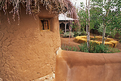 """Carol Anthony's adobe """"santuario"""" is embelished by a roof of twigs and a thick stucco wall which embraces it and her small  tin roofed casita."""