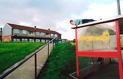 Boy playing on top of bus shelter next to run down local authority housing estate; Bradford; Yorkshire UK