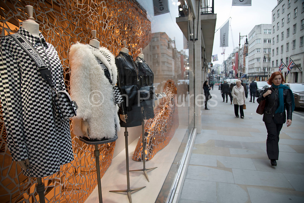 Exclusive clothes shop window of Dior on New Bond Street in Mayfair, London, England, United Kingdom. Bond Street is one of the principal streets in the West End shopping district and is very upmarket. It has been a fashionable shopping street since the 18th century. The rich and wealthy shop here mostly for high end fashion and jewellery.