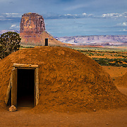 Native American hogans and Mitchell Butte  in Monument Valley Tribal Park of the Navajo Nation, AZ.