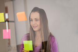 Young woman planning sticking post-its on glass