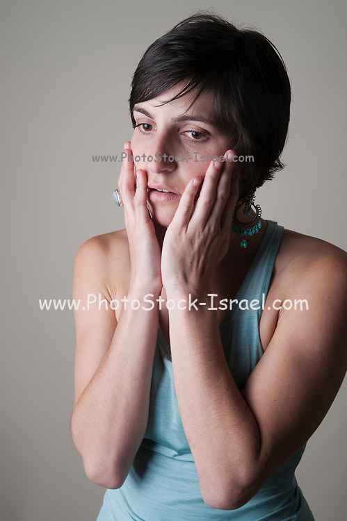 Studio shot of a fearful female model in her 20s on white background