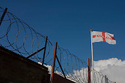 With coils of barded security wire beneath, a sad-looking English flag on a pole overlooks an industrial yard in south London. This might be a metaphor for the state of the nation today, a dystopian society of pessimism and oppression as if from Orwellian fiction. It may also suggest a country during revolution or quanrantine, closed behind the security fence.