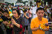 "25 FEBRUARY 2013 - BANGKOK, THAILAND:  Thais pray in front of Wat Benchamabophit Dusitvanaram (popularly known as either Wat Bencha or the Marble Temple) on Makha Bucha Day. Thais visit temples throughout the Kingdom on Makha Bucha Day to make merit and participate in candle light processions around the temples. Makha Bucha is a Buddhist holiday celebrated in Myanmar (Burma), Thailand, Cambodia and Laos on the full moon day of the third lunar month (February 25 in 2013). The third lunar month is known in Thai is Makha. Bucha is a Thai word meaning ""to venerate"" or ""to honor"". Makha Bucha Day is for the veneration of Buddha and his teachings on the full moon day of the third lunar month. Makha Bucha Day marks the day that 1,250 Arahata spontaneously came to see the Buddha. The Buddha in turn laid down the principles his teachings. In Thailand, this teaching has been dubbed the 'Heart of Buddhism'.     PHOTO BY JACK KURTZ"