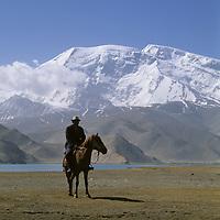 CHINA, Xinjiang. Khyrgiz nomad rides by Lake Karakul. 7546m Mustagh Ata (Pamir Mountains)