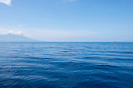 A small cargo boat plies through the Bismarck Sea on a five-hour journey from Karkar Island (left) to the mainland of Papua New Guinea. Karkar is a volcanic island in Madang Province.