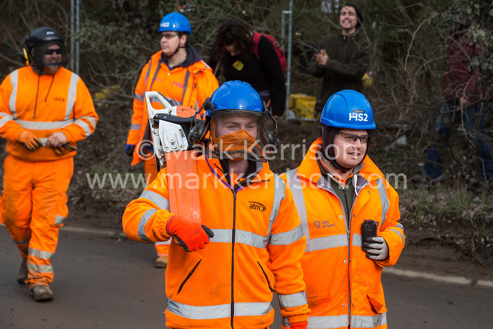Harefield, UK. 8 February, 2020. HS2 engineers retreat with a chainsaw after being prevented from felling trees for the high-speed rail project by environmental activists from Save the Colne Valley, Stop HS2 and Extinction Rebellion. The activists were successful in preventing any of the scheduled tree felling by HS2 and after an intervention by a police officer all tree felling and strimming work has now been cancelled for the weekend.