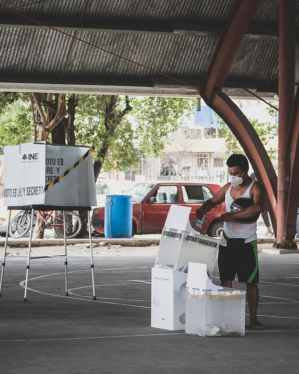 Tulum, Mexico - June 6, 2021: A man casts his ballot at a precinct in Tulum during Mexico's mid-term elections.