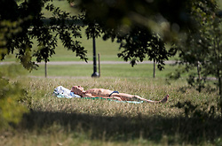 © Licensed to London News Pictures. 14/09/2020. London, UK. A man is seen relaxing in the warm weather on Primrose Hill in North London as the UK Experiences a mini heatwave. New Coronavirus restrictions introduced today prevent people from gathering in groups of more than six. Photo credit: Ben Cawthra/LNP