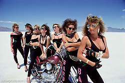 """The Bad Barbies. Bonneville Salt Flats, UT. 1989<br /> <br /> Limited Edition Print from an edition of 50. Photo ©1989 Michael Lichter.<br /> <br /> The Story: The Easyriders' Streamliner broke the world's land speed record at 322 mph and seven beautiful women who call themselves the """"Bad Barbies"""" appeared out of nowhere. The Bonneville Salt Flats are surreal, but I still wonder who were these women and where did they come from?"""
