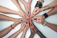 Women's hands in a geometric connection design photographed on a white background.