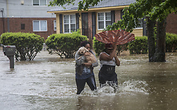 April 25, 2017 - Raleigh, North Carolina, U.S. - NAUTICAL JACKSON, left, and ANIYA RUFFIN walk through floodwaters with their dog, Chestnut, as water threatens to enter their home on Dacian Road. (Credit Image: © Travis Long/TNS via ZUMA Wire)
